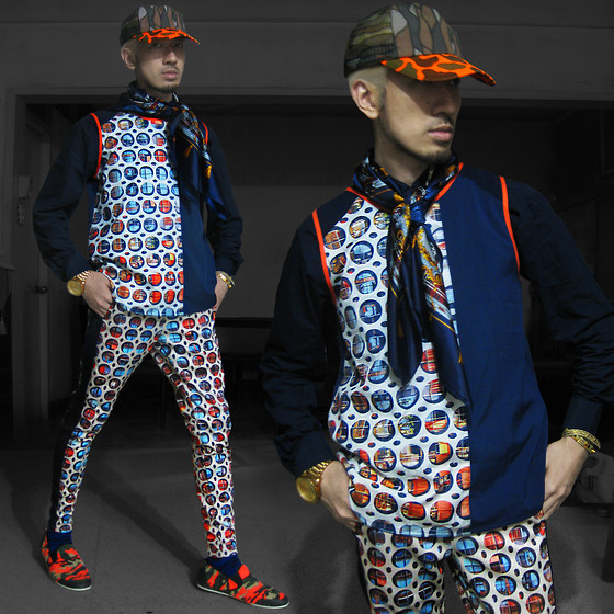 Andre Judd - Vintage Camo Cap With Fluoro Orange Brim, Sleeveless Tank With Digi Hole Print, Trousers With Digi Hole Print, Zebra Print Socks, Camo Print Canvas Slipons, Python Bracelet, Silk Scarf - HOLEY CAMOLEY