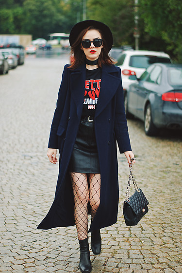 Andreea Birsan - Black Fedora Hat, Long Navy Coat, Graphic T Shirt, Leather Mini Skirt, Leather Ankle Boots, Fishnet Tights, Choker Necklace, Leather Quilted Crossbody Bag, Cat Eye Sunglasses - Leather skirt & long navy coat: How to stay warm this fall