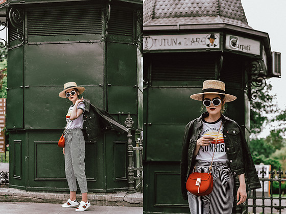 Andreea Birsan - Leather Trucker Jacket, Striped Pants, Graphic T Shirt, White Leather Ace Sneakers, White Sunglasses, Straw Boater Hat, Red Crossbody Bag - Striped pants