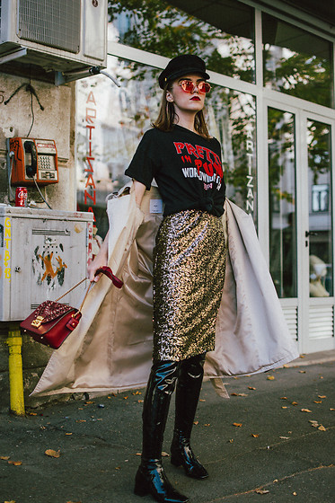 Andreea Birsan - Graphic T Shirt, Baker Boy Cap, Red Tinted Sunglasses, Hoop Earrings, Ruby Red Lace Trim Metropolis Shoulder Bag, Slit Midi Sequin Skirt, Beige Trench Coat, Patent Over The Knee Boots - Sequin skirt & punk tee