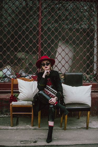 Andreea Birsan - Red Fedora Hat, Black Double Breasted Military Coat, Skinny Vinyl Trousers, Black Heeled Sock Boots, Red Socks, Punk T Shirt, Striped Bag With Eyelet Details, Gold Hoop Earrings, Black Cat Eye Sunglasses - Waiting game