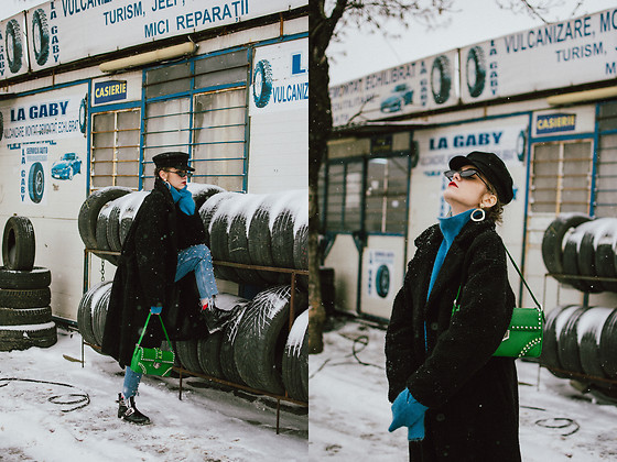 Andreea Birsan - Baker Boy Hat, Small Cat Eye Sunglasses, Blue Cashmere Turtleneck Sweater, Black Teddy Bear Coat, Prada Green Shoulder Bag With Studs And Stones, Pearl Embellished Mom Jeans, Patent Biker Boots With Buckles, Statement Earrings - Cold weather essentials