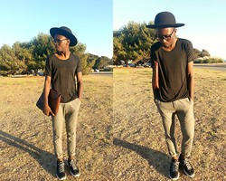 Ronald Gravesande - Zara Dark Grey Draped T Shirt, Asos Light Grey Trousers, Nike Black And Grey Sneakers, Urban Outfitters Black Hat, Zara Brown Leather Crocodile Clutch - The Road is Draped in Grey