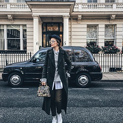 Andreea Birsan - Marina Cap, Glasses, Khaki Military Coat, Grey Bell Sleeve Sweater, White Button Down Shirt, Khaki Pants, Embroidered Crossbody Bag, Glitter Socks, White Stan Smith Sneakers - Blending in