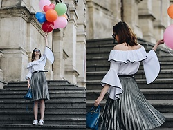 Andreea Birsan - Contrast Frilled Off Shoulder Top, Midi Silver Metallic Pleated Skirt, Borsa A Mano Saffiano Lux Cobalt Bag, Leather Belt, Heart Embroidered White Sneakers, Square Blue Sunglasses - Celebration