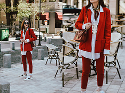 Andreea Birsan - Red Blazer, Red Trousers, Oversize White Button Down Shirt, White Lace Up Corset, Ace Sneakers, Square Sunglasses, Red Lace Shoulder Bag - A fashion forward way to styling a suit