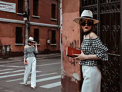 Andreea Birsan - Gingham Off Shoulder Top, White Wide Leg Pants, White Straw Fedora Hat, Suede Heeled Mules, Round Sunglasses, Scarf - How to look polished when traveling
