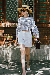 Andreea Birsan - Vintage Inspired Bag, Straw Boater Hat, Statement Earrings, Black Cat Eye Sunglasses, Balloon Sleeve Polka Dot Tie Back Top, White High Waisted Shorts, White Leather Pumps - Vintage inspired bag
