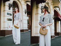 Andreea Birsan - White Wide Leg Trousers, White Flat Studded Mules, Mini Straw Bag, Polka Dot Tie Front Shirt, Cat Eye Sunglasses, Red Statement Earrings - The wide leg trousers
