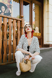 Andreea Birsan - Pom Pom Earrings, Polka Dot Tie Front Shirt, Cat Eye Sunglasses, White Wide Leg Trousers, Studded White Flat Mules, Mini Basket Bag - The statement earrings