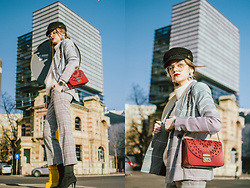 Andreea Birsan - Check Printed Blazer, Baker Boy Cap, Clear Lens Aviator Glasses, Statement Earrings, Ruby Red Metropolis Shoulder Bag, Checked Flared Cropped Trousers, Black Heeled Sock Boots, Beige Cashmere Sweater - Check printed blazer: what to wear to work in 2018