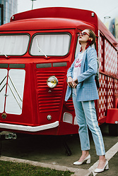 Andreea Birsan - White Leather Heeled Shoes, Statement Jeans With Side Pannel, Baby Blue Checked Blazer, White T Shirt With Print, Red Pom Pom Statement Earrings, Red Small Cat Eye Sunglasses - The statement jeans