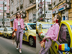 Andreea Birsan - Cropped Pink Jacket, White Cami Top, Purple Peg Trousers, White Block Heel Shoes, Mini Tote Bag, Red Pom Pom Earrings, Clear Lens Aviator Glasses - Pink and purple