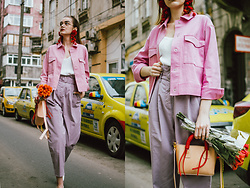 Andreea Birsan - Pink Cropped Jacket, White Cami Top, Red Pom Pom Earrings, Clear Lens Aviator Glasses, Purple Peg Trousers, Statement Mini Tote Bag, White Pumps - Spring pastels: pink and purple
