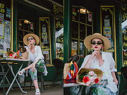 Andreea Birsan - White Linen Shirt, White Cami Top, Straw Boater Hat, Small Cat Eye Sunglasses, Striped Silk Scarf, Straw Bag With Wooden Handle, Floral Earrings, Floral Print Trousers, White Ace Heart Embroidered Sneakers - The eye-catching floral print trousers