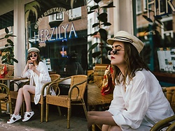Andreea Birsan - White Linen Shirt, Striped Linen Shorts, Straw Baker Boy Hat, Small Sunglasses, Ark Bag, Heart Embroidered Sneakers - The white shirt