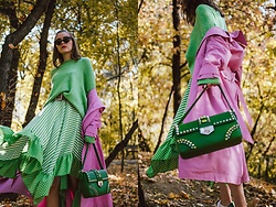 Andreea Birsan - Green Sweater, Black Cat Eye Sunglasses, Green Asymmetric Midi Polka Dot And Stripes Skirt, Green Shoulder Bag, Pink Trench Coat - Pink and green
