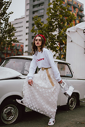 Andreea Birsan - White Sweatshirt, Red Beret, Gold Metallic Belt, White Maxi Skirt, Clear Lens Glasses, Transparent Tote Bag, Ace Heart Embroidered White Sneakers - Winter whites