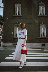 Andreea Birsan - Graphic T Shirt, Belt, Black Cat Eye Sunglasses, Red Prada Bag, White Midi Pleated Skirt, Two Tone Sneakers - All white outfit