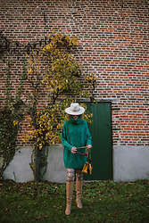 Andreea Birsan - Beige Fedora Hat, Roll Neck Green Chunky Sweater, Velvet Brown And Yellow Shoulder Bag, Beige Knee High Boots, Logo Stockings - Chunky sweater