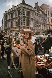 Andreea Birsan - Beige Boater Hat, Clear Lens Glasses, Long Brown Coat, Beige Bag - Neutrals on repeat